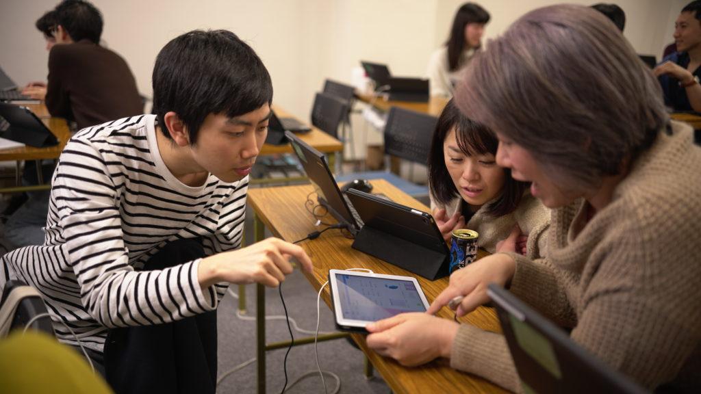 3人の受講生がパソコンを持って真剣に取り組んでいる