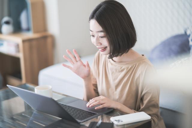 リモートでパソコンに向かい笑顔で話す女性
