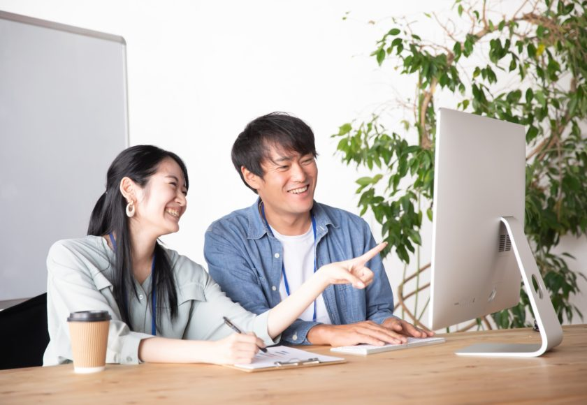 パソコンに向かう笑顔の男女
